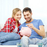 couple-on-couch-putting-money-in-piggy-bank
