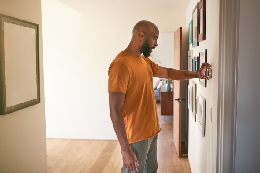 Man checking if thermostat is broken